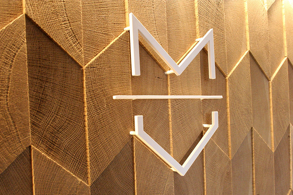 close up of steel logo on textured wood feature wall