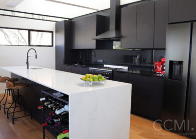 A black kitchen that is anything but dull and dreary – natural light and a white marble island