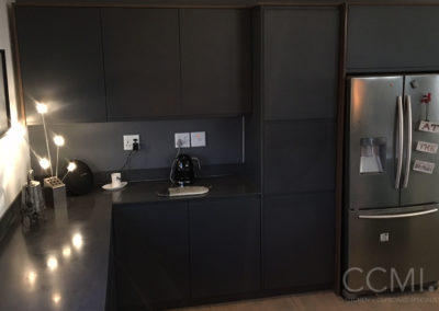 matte black kitchen with partially reflective countertops and interesting mood lighting