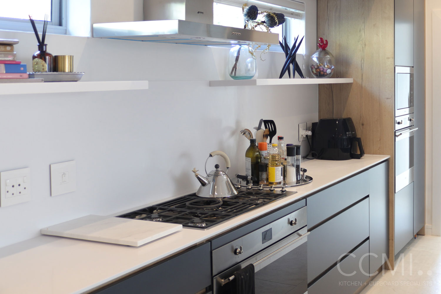 artwork displayed in the kitchen on floating shelves creates points of interest in the design