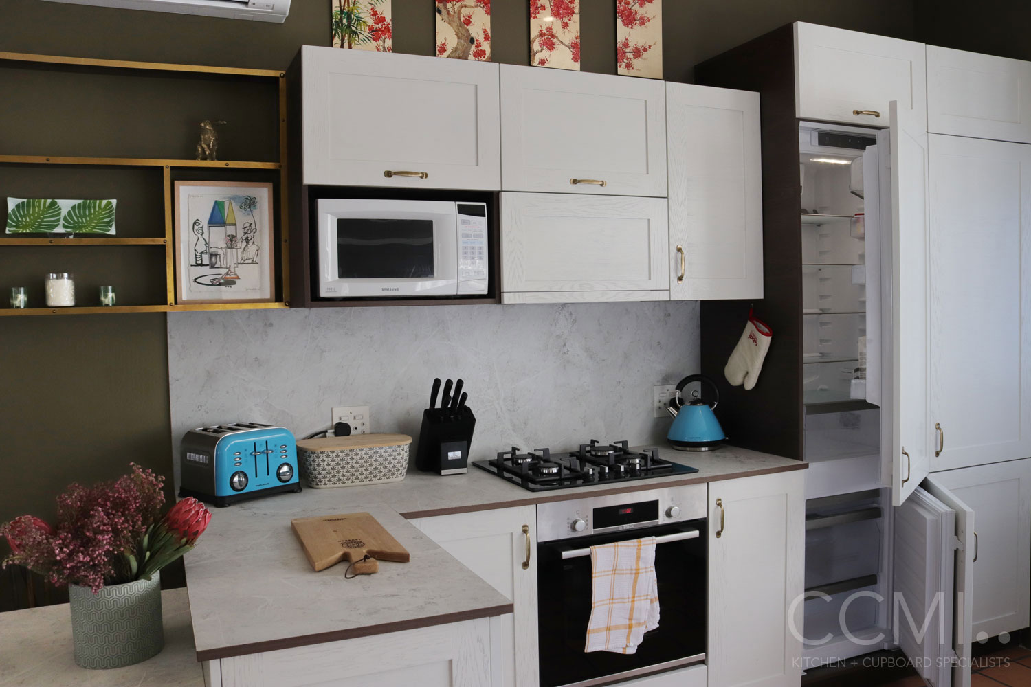 integrated large appliances (such as this fridge) are cleverly hidden to allow this small kitchen to appear less cluttered