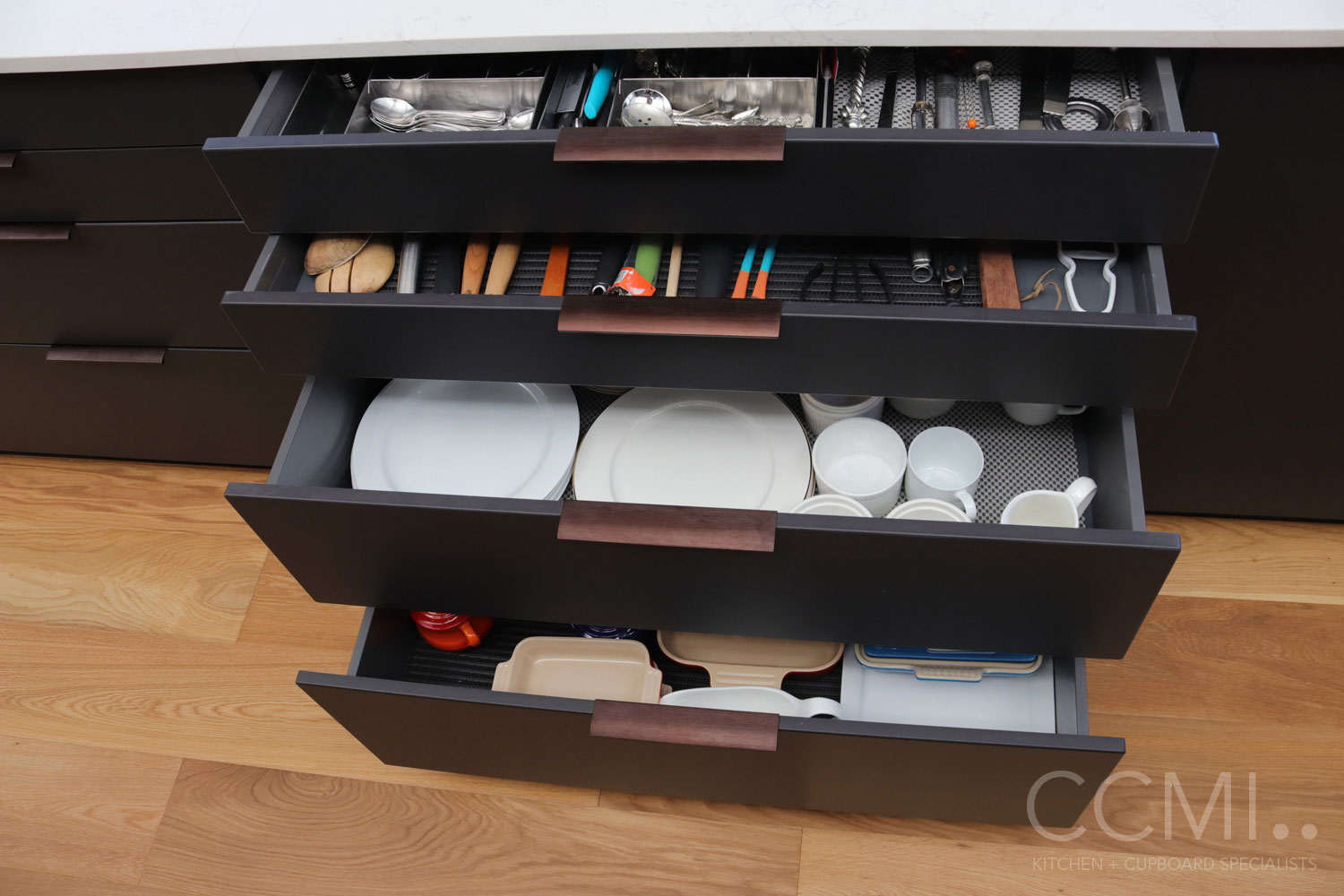 drawers in the kitchen island provide storage for utensils, cutlery, and crockery