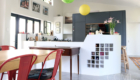 an irregular shaped kitchen island accommodates a hob, wine storage/display shelf with an elevated counter that serves as a bar