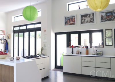 white kitchen cabinets and countertops emphasise the lightness of the room