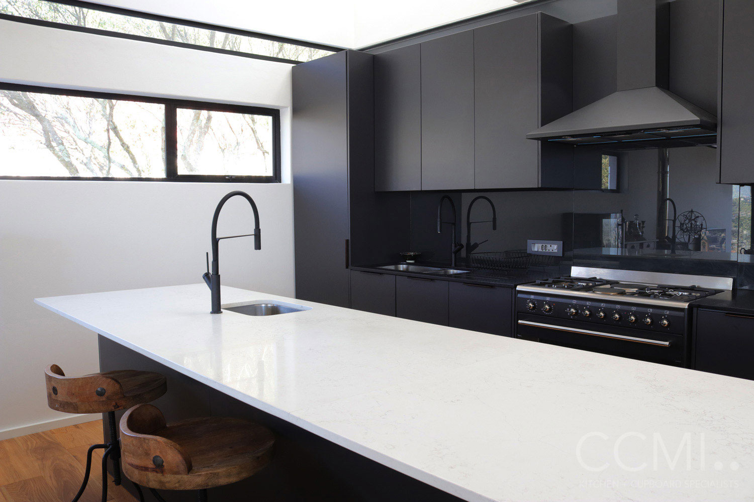 a matte black mixer and prep bowl is set in the white marbled kitchen island