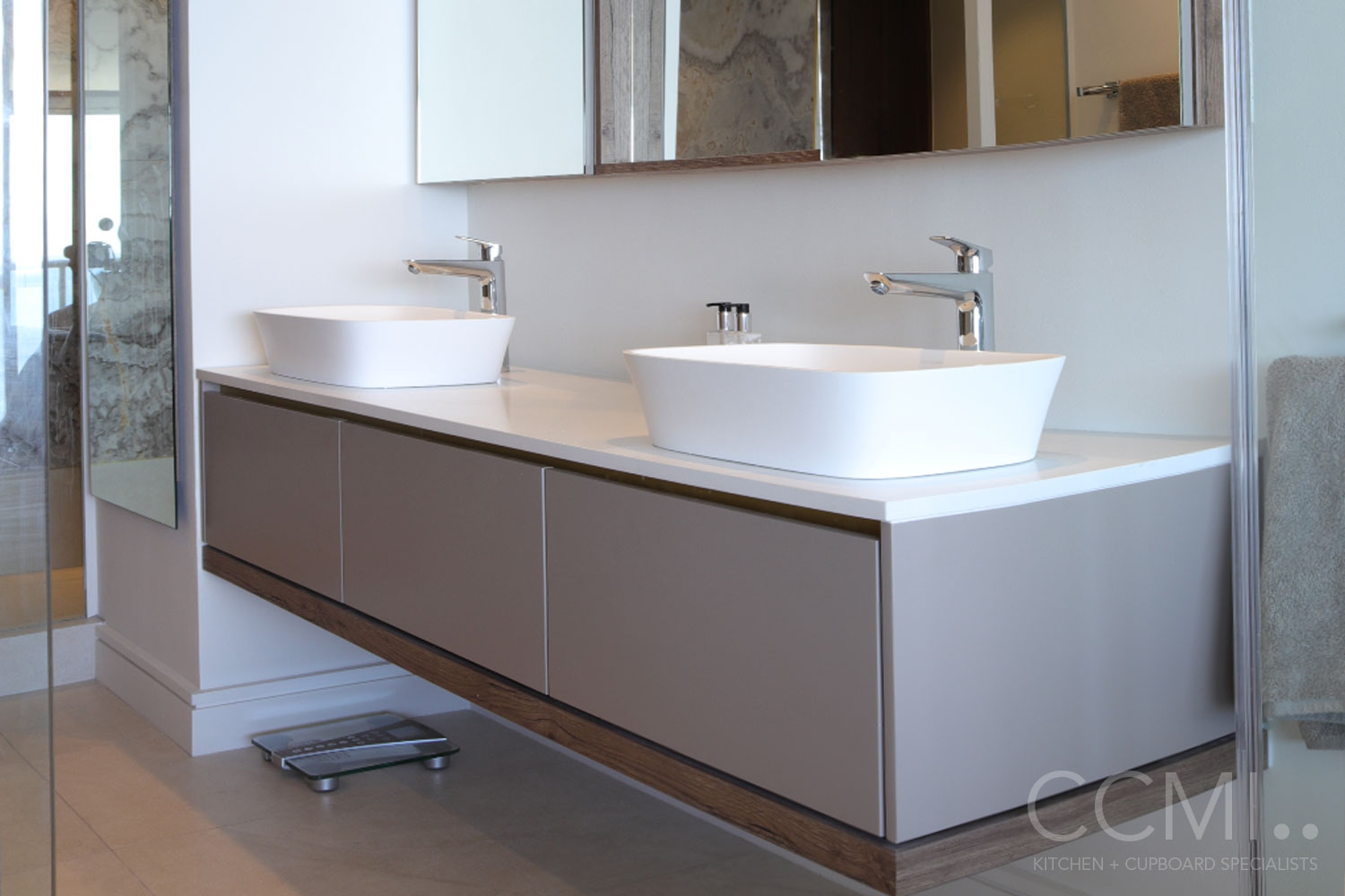 floating double vanity with vessel sinks and custom mirrors